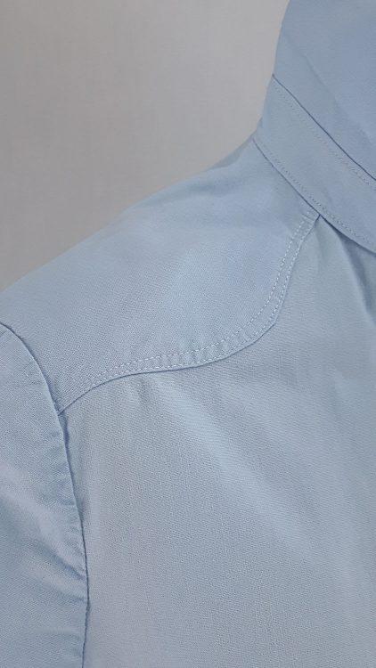 Vue de détail d'un chemisier bleu ciel avec empiècement d'épaule courbe, zoom sur l'empiècement arrondi en haut du devant - modèle exemple des ateliers Rêve à Soie
