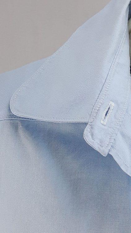 Vue de détail d'un chemisier bleu ciel avec empiècement d'épaule courbe, zoom sur le col chemisier surpiqué - modèle exemple des ateliers Rêve à Soie