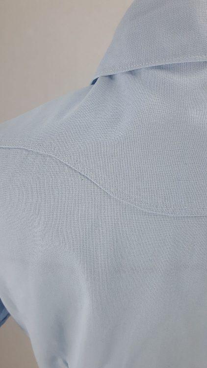 Vue de détail d'un chemisier bleu ciel avec empiècement d'épaule courbe, zoom sur l'empiècement arrondi en haut du dos - modèle exemple des ateliers Rêve à Soie