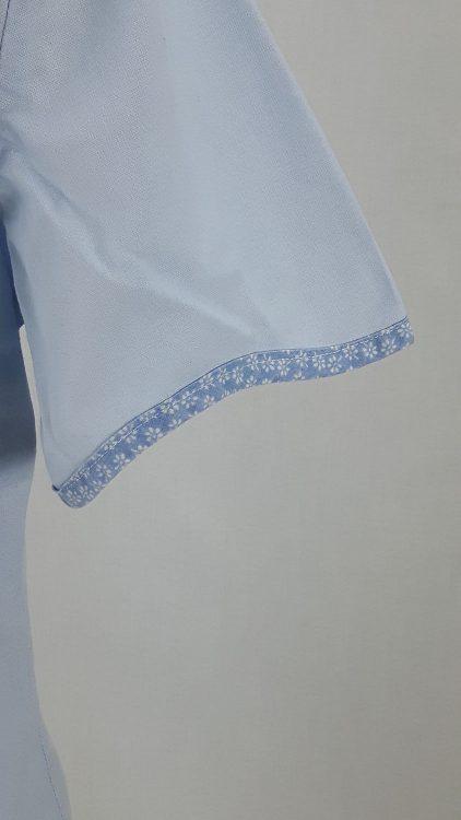 Vue de détail d'un chemisier bleu ciel avec empiècement d'épaule courbe, zoom le bas de manche bordé de biais - modèle exemple des ateliers Rêve à Soie