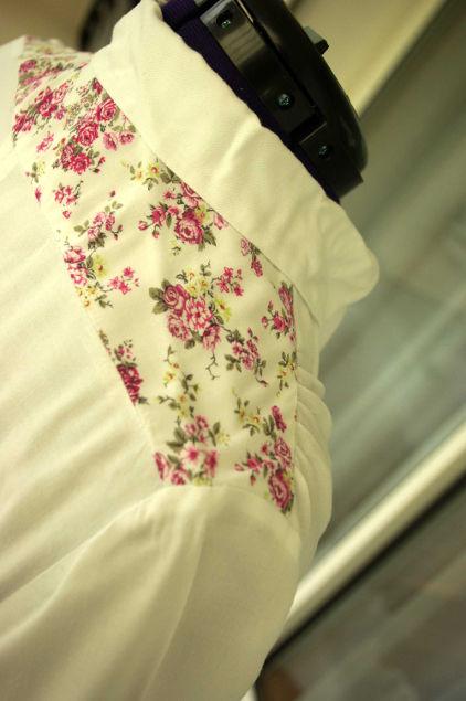 Vue de détail d'un chemisier blanc avec empiècement d'épaules à fleurs, zoom sur l'empiècement d'épaule et le col - modèle exemple des ateliers Rêve à Soie