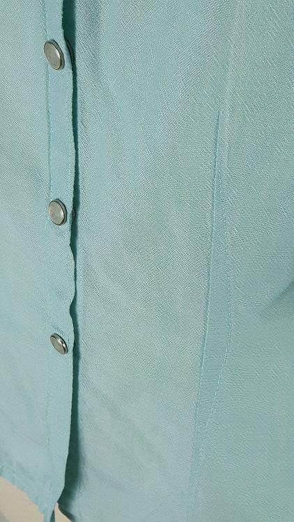 Vue de détail d'un chemisier en coton vert d'eau à manches raglan, zoom sur la croisure milieu devant et le bas du chemisier - modèle exemple des ateliers Rêve à Soie
