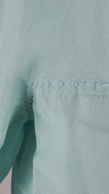 Vue de détail d'un chemisier en coton vert d'eau à manches raglan, zoom sur la couture raglan horizontale au niveau du dessous de bras - modèle exemple des ateliers Rêve à Soie