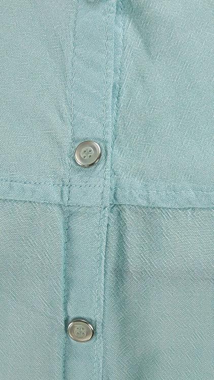 Vue de détail d'un chemisier en coton vert d'eau à manches raglan, zoom sur les pressions du milieu devant et la couture raglan horizontale - modèle exemple des ateliers Rêve à Soie