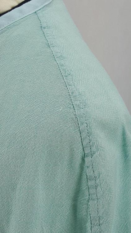 Vue de détail d'un chemisier en coton vert d'eau à manches raglan, zoom sur la couture d'épaule et le biais d'encolure - modèle exemple des ateliers Rêve à Soie