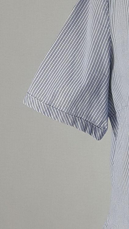 Vue de détail d'un chemisier manches courtes en tissu rayé bleu, zoom sur le bas de manche bordé de biais large - modèle exemple des ateliers Rêve à Soie