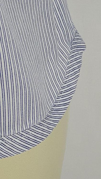 Vue de détail d'un chemisier manches courtes en tissu rayé bleu, zoom sur le bas en forme de vague - modèle exemple des ateliers Rêve à Soie