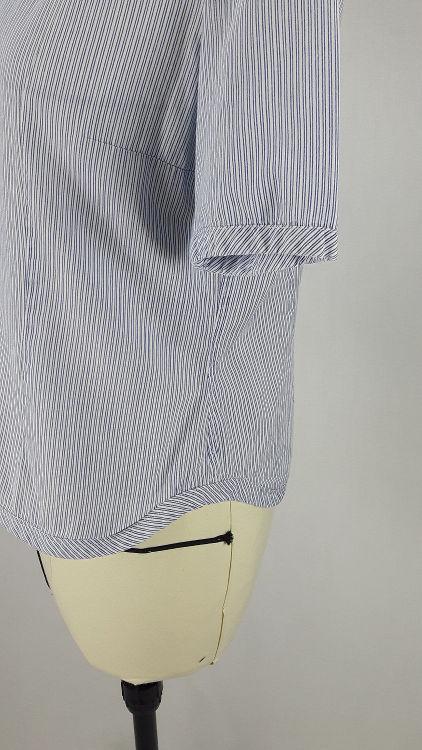 Vue de détail d'un chemisier manches courtes en tissu rayé bleu, zoom sur le bas en forme de vague et le bas de manche bordé de biais large - modèle exemple des ateliers Rêve à Soie