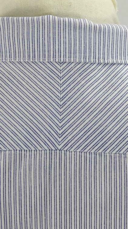 Vue de détail d'un chemisier manches courtes en tissu rayé bleu, zoom sur le haut du dos et la couture plein biais de l'empiècement - modèle exemple des ateliers Rêve à Soie