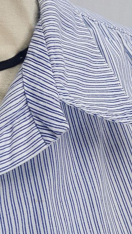 Vue de détail d'un chemisier manches courtes en tissu rayé bleu, zoom sur le col chemisier devant et son pied de col en biais - modèle exemple des ateliers Rêve à Soie