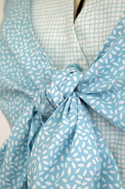 Vue de détail d'une robe d'été sans manche réalisée en deux tissus à dominante turquoise, vue zoomée sur le cache-cœur noué - modèle d'une élève des ateliers Rêve à Soie