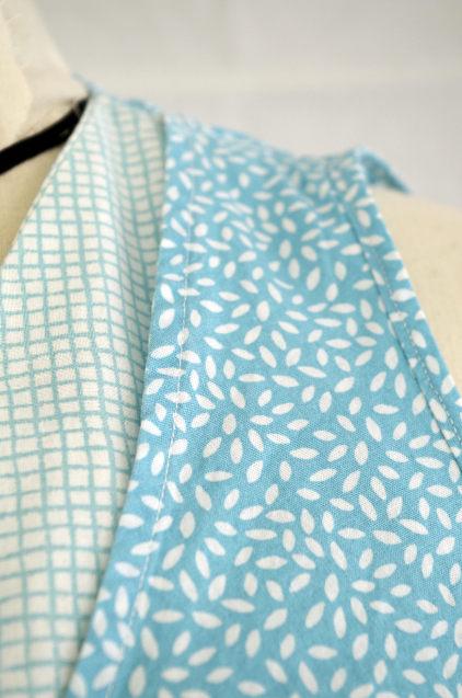Vue de détail d'une robe d'été sans manche réalisée en deux tissus à dominante turquoise, zoom sur l'épaule et le bord d'emmanchure bordé de biais et surpiqué - modèle d'une élève des ateliers Rêve à Soie