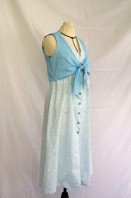 Vue de face d'une robe d'été sans manche réalisée en deux tissus à dominante turquoise, boutonnée sur le milieu devant, avec une partie haute en effet cache-cœur - modèle d'une élève des ateliers Rêve à Soie