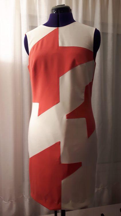 Vue de face d'une robe à découpes en forme de grand pied de poule en crêpe crème et corail - modèle exemple des ateliers Rêve à Soie