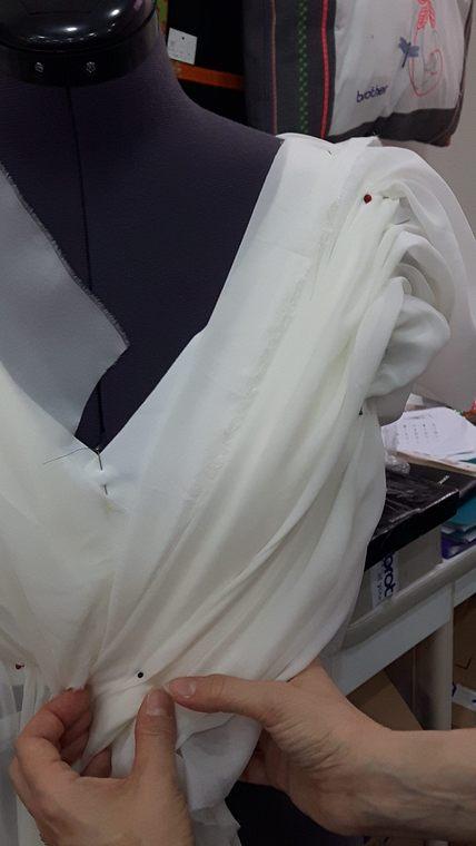 Vue de face du haut d'une robe de mariée, essai de drapé en diagonale dans la mousseline de la sur-robe le long d'une encolure en V - modèle d'une élève des ateliers Rêve à Soie