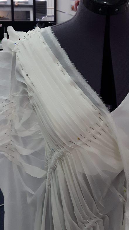 Vue de face du haut d'une robe de mariée, essai de plissé dans la mousseline de la sur-robe le long d'une encolure en V - modèle d'une élève des ateliers Rêve à Soie