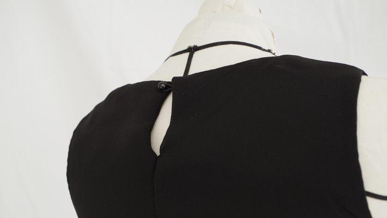 Vue de dos d'un top en mousseline noire bi-épaisseurs de longueurs différentes, fermeture avec goutte d'eau dans le dos - modèle d'une élève des ateliers Rêve à Soie