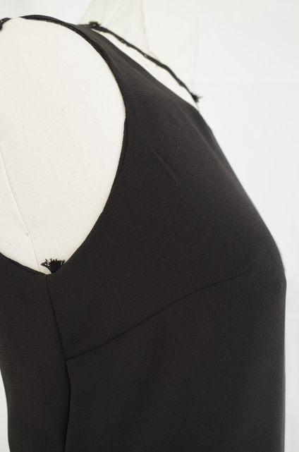 Vue de profil d'un top en mousseline noire bi-épaisseurs de longueurs différentes, fermeture avec goutte d'eau dans le dos - modèle d'une élève des ateliers Rêve à Soie