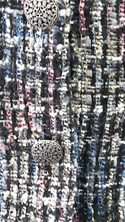 """Vue de détail d'une veste style """"petite veste Chanel"""" droite et sans col dans un tissu en lainage multi-colore, zoom sur les boutons en métal - modèle d'une élève des ateliers Rêve à Soie"""