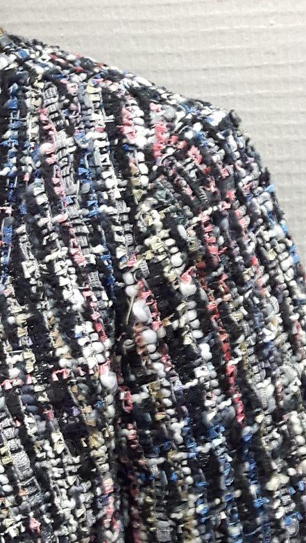 """Vue de détail d'une veste style """"petite veste Chanel"""" droite et sans col dans un tissu en lainage multi-colore, zoom sur le haut de la manche - modèle d'une élève des ateliers Rêve à Soie"""