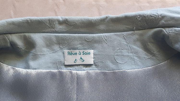 Photo zoomant sur le haut de l'intérieur d'une veste bleu ciel où est cousue une étiquette griffée au logo Rêve à Soie