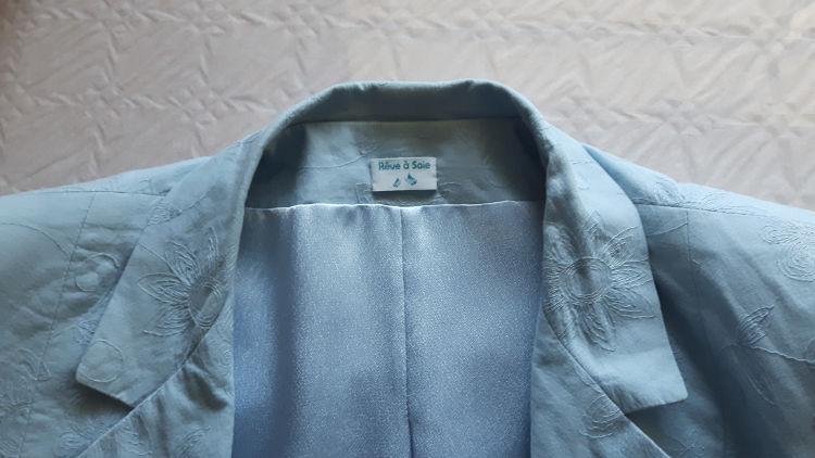 Photo d'ensemble de l'intérieur d'une veste bleu ciel où est cousue une étiquette griffée au logo Rêve à Soie