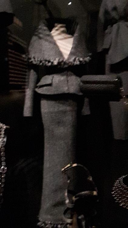 Tailleur miniature gris foncé : veste très cintrée avec très large col châle tombant sur les épaules et jupe droite très longue- Exposition Dior 2017