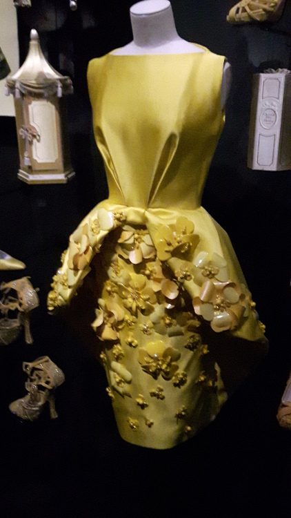 Robe jaune à plis sur le haut et grand basque avec nœuds cousus - Exposition Dior 2017