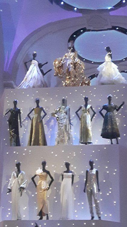 Vue d'ensemble de tenues du soir dorées, blanches, noires ou argentées - Exposition Dior 2017