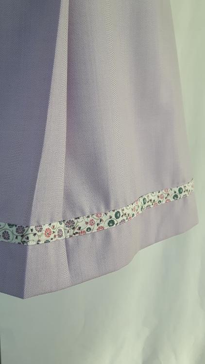 Vue de détail d'une jupe mauve avec pli asymétrique et forme trapèze. Zoom sur le bas de l'ourlet et le biais - modèle exemple des ateliers Rêve à Soie